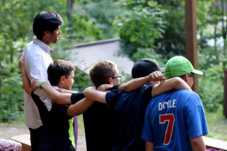 4 boys and their cabin leader with arms around each other at evening program