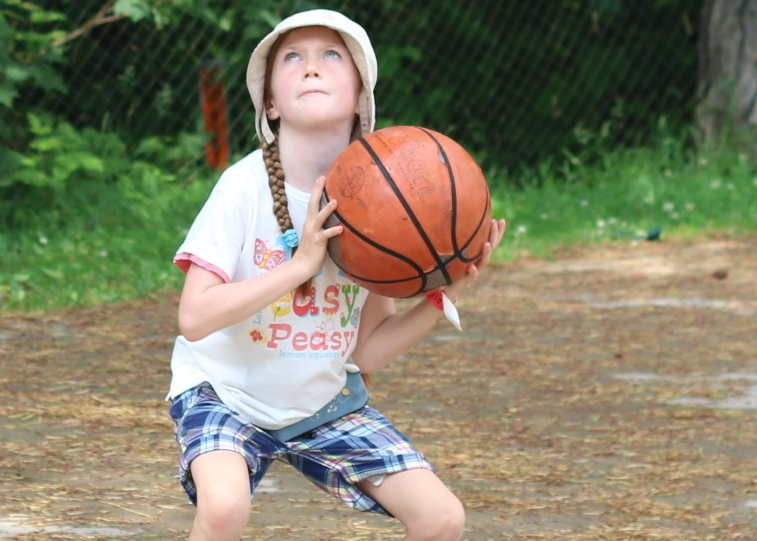 Camper playing basketball outside at Christian Adventure Summer Camp in Haliburton, Ontario