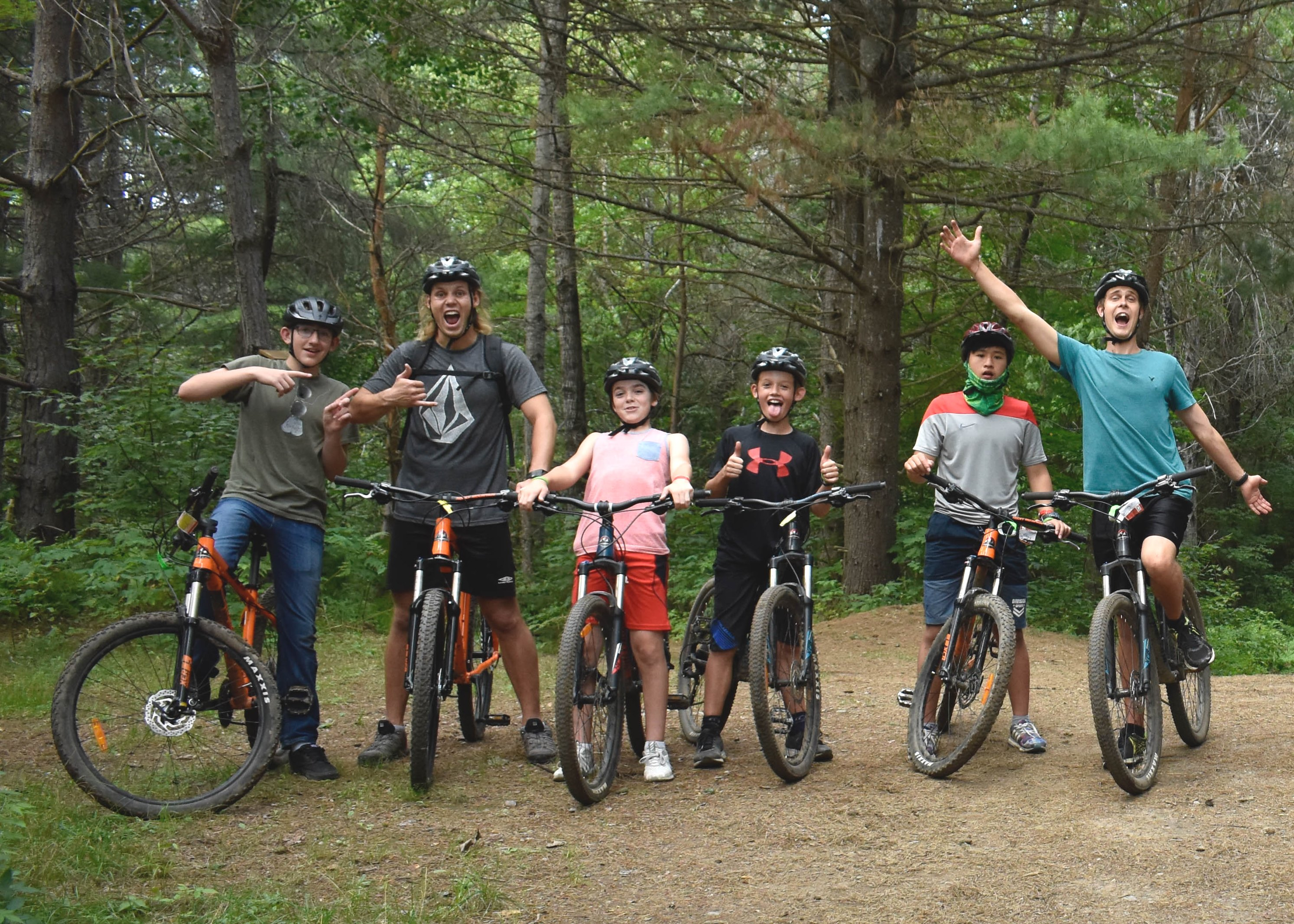 Campers mountain biking in woods at christian adventure summer camp in Haliburton, Ontario