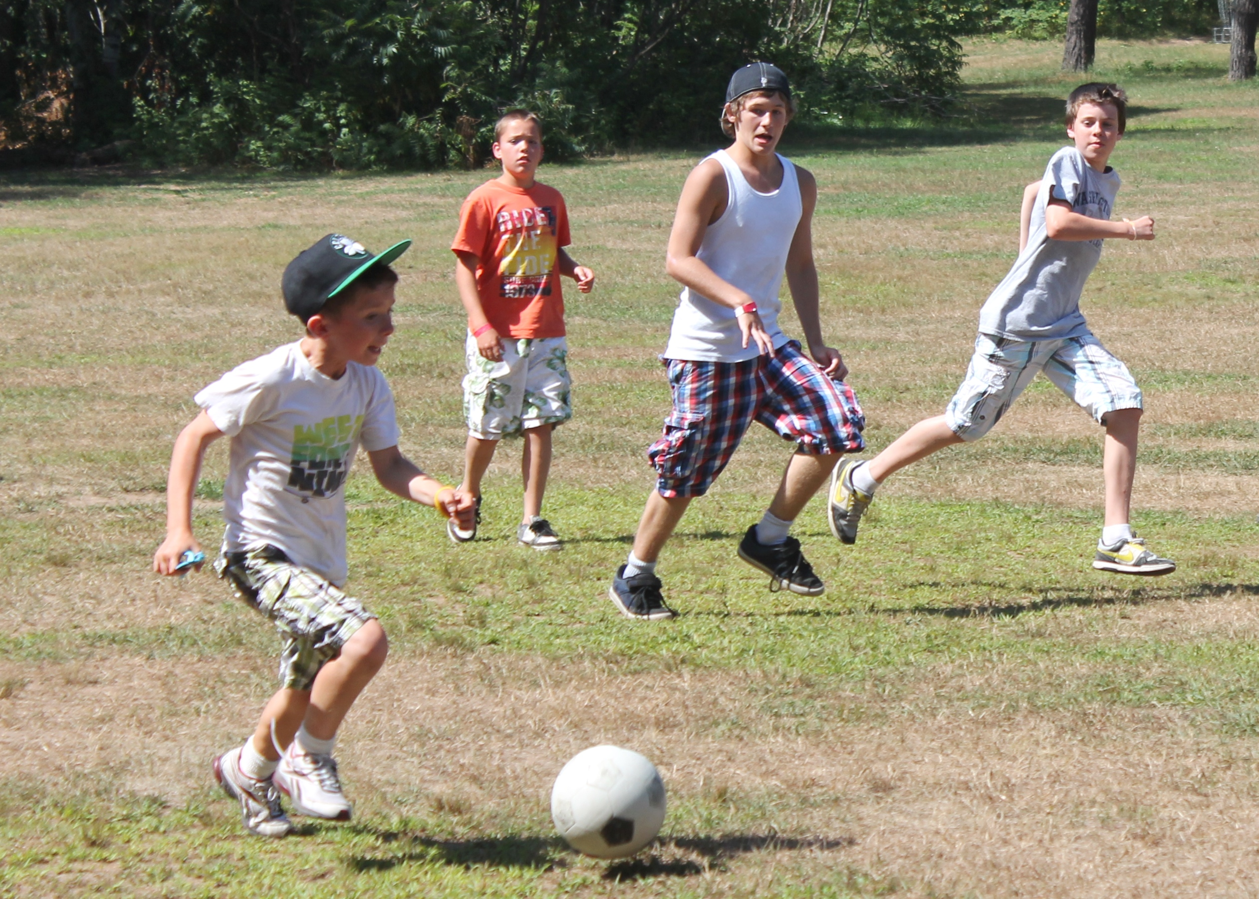 Campers playing soccer outside at christian adventure summer camp in Haliburton, Ontario