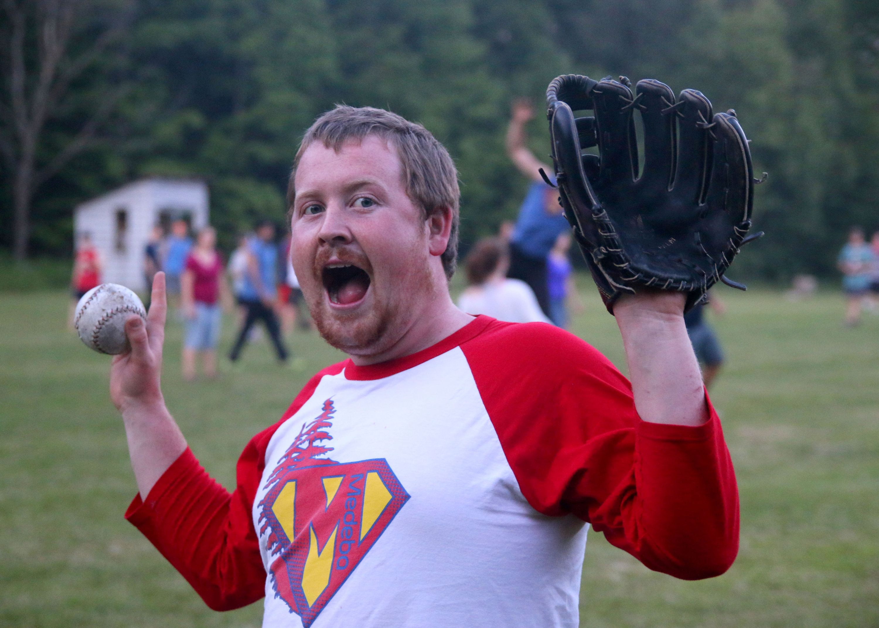 Staff member playing baseball outside at Christian Adventure Summer Camp