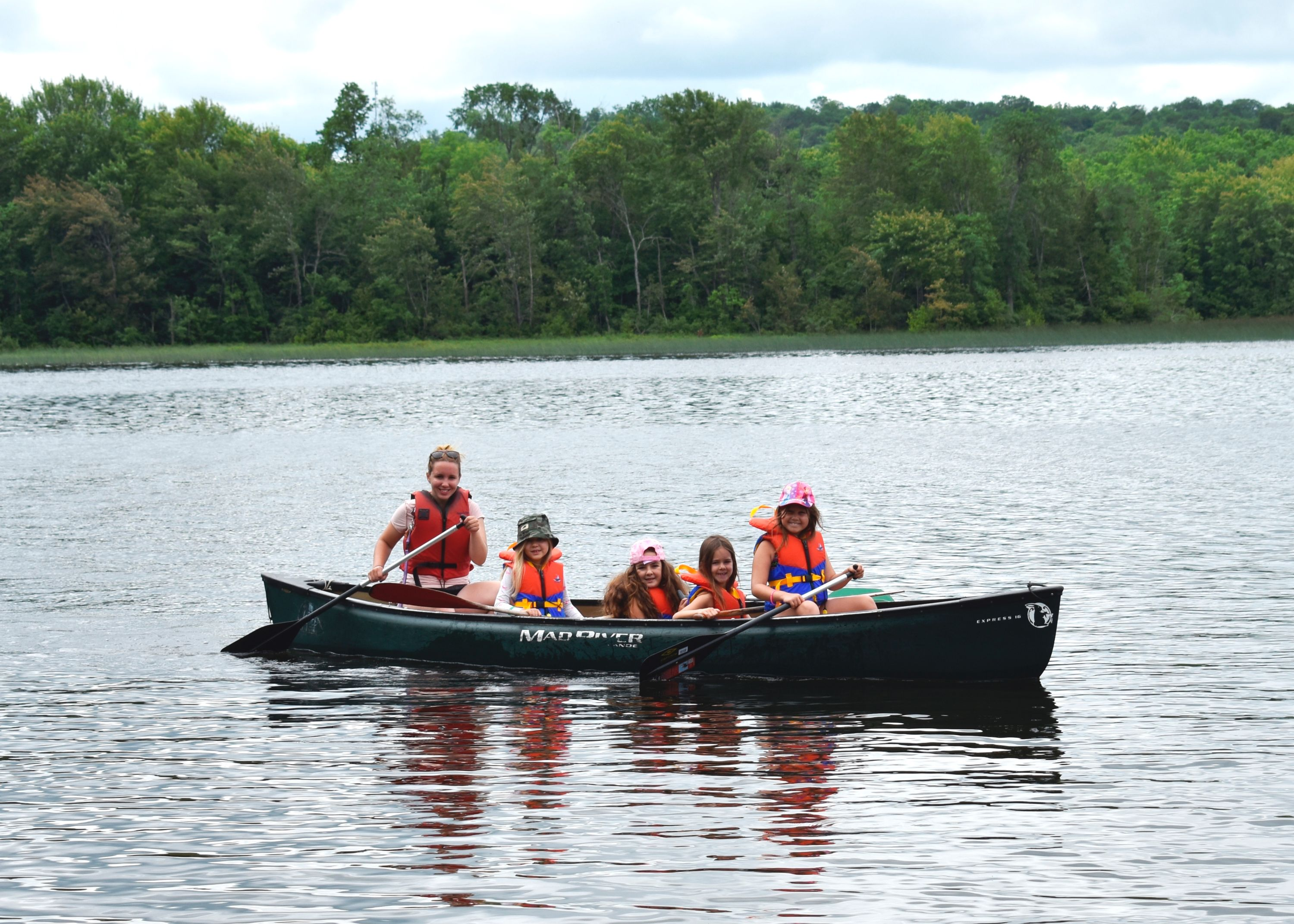 Campers canoeing in lake in West Guilford, Ontario as a part of a Christian Adventure Summer Camp