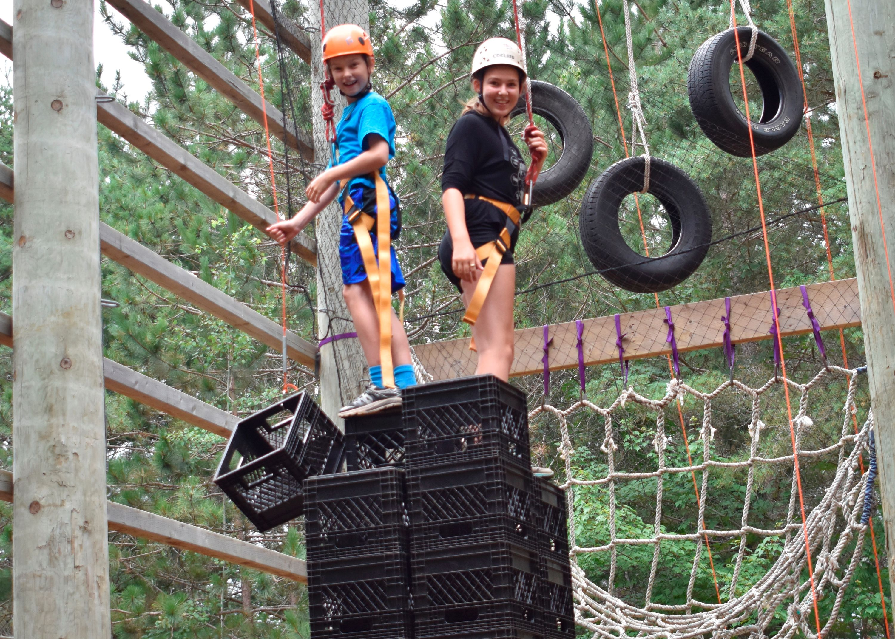 Campers building milk crate tower for a vertical team challenge at christian adventure summer camp in Haliburton, Ontario