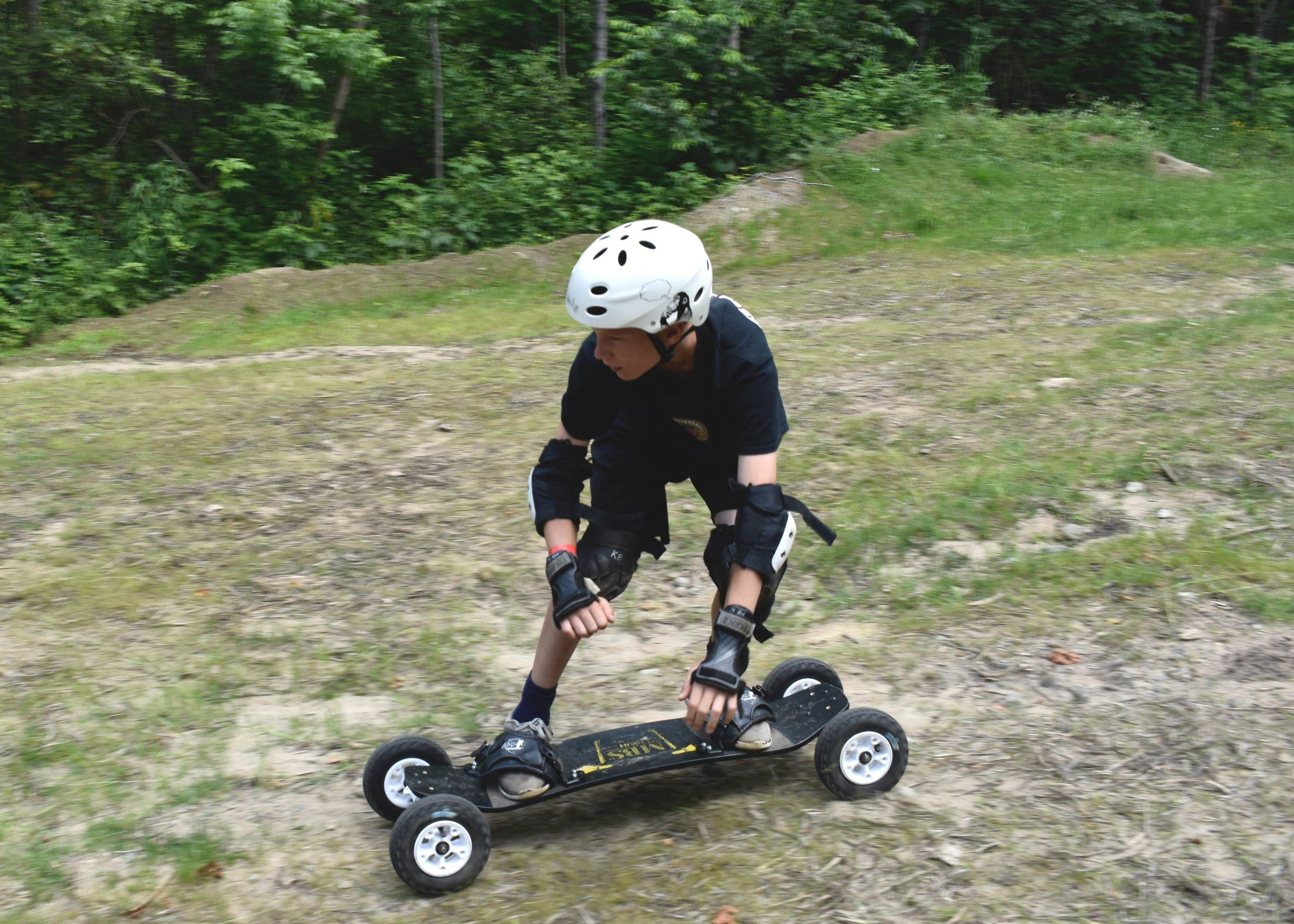 Camper mountain boarding outside at christian adventure summer camp in Haliburton, Ontario