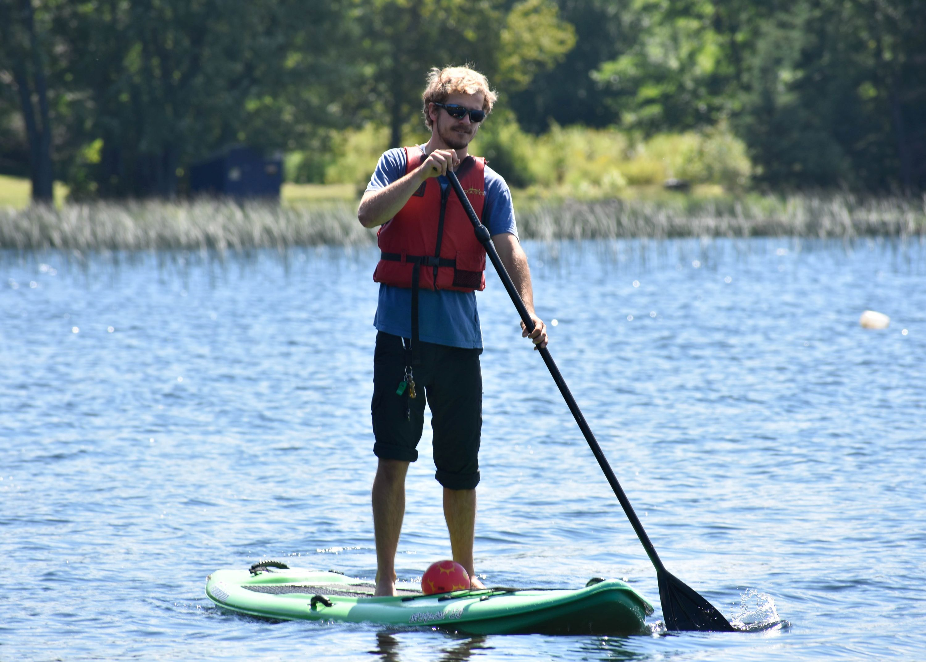 Staff paddling a stand up paddle board on lake in West Guilford, Ontario's Christian Adventure Summer Camp