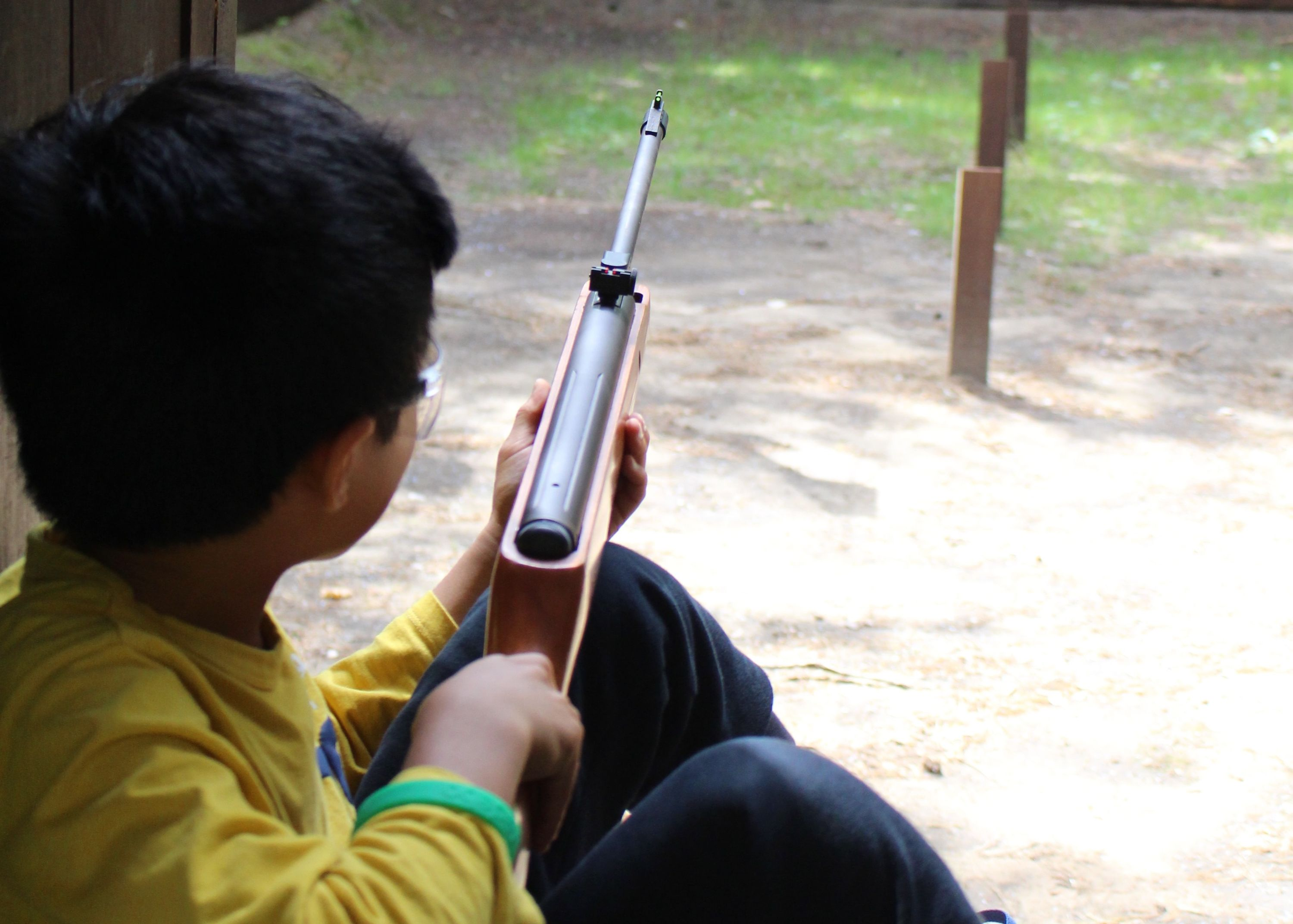 Camper enjoying riflery outside at Adventure Summer Camp