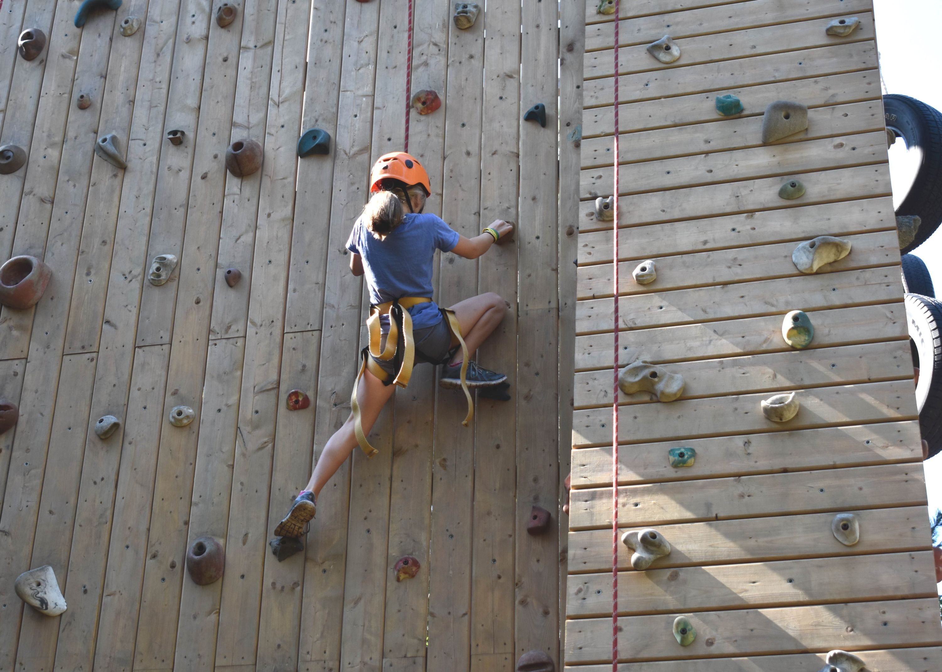 Camper climbing outdoor rock wall at christian adventure summer camp in Haliburton, Ontario