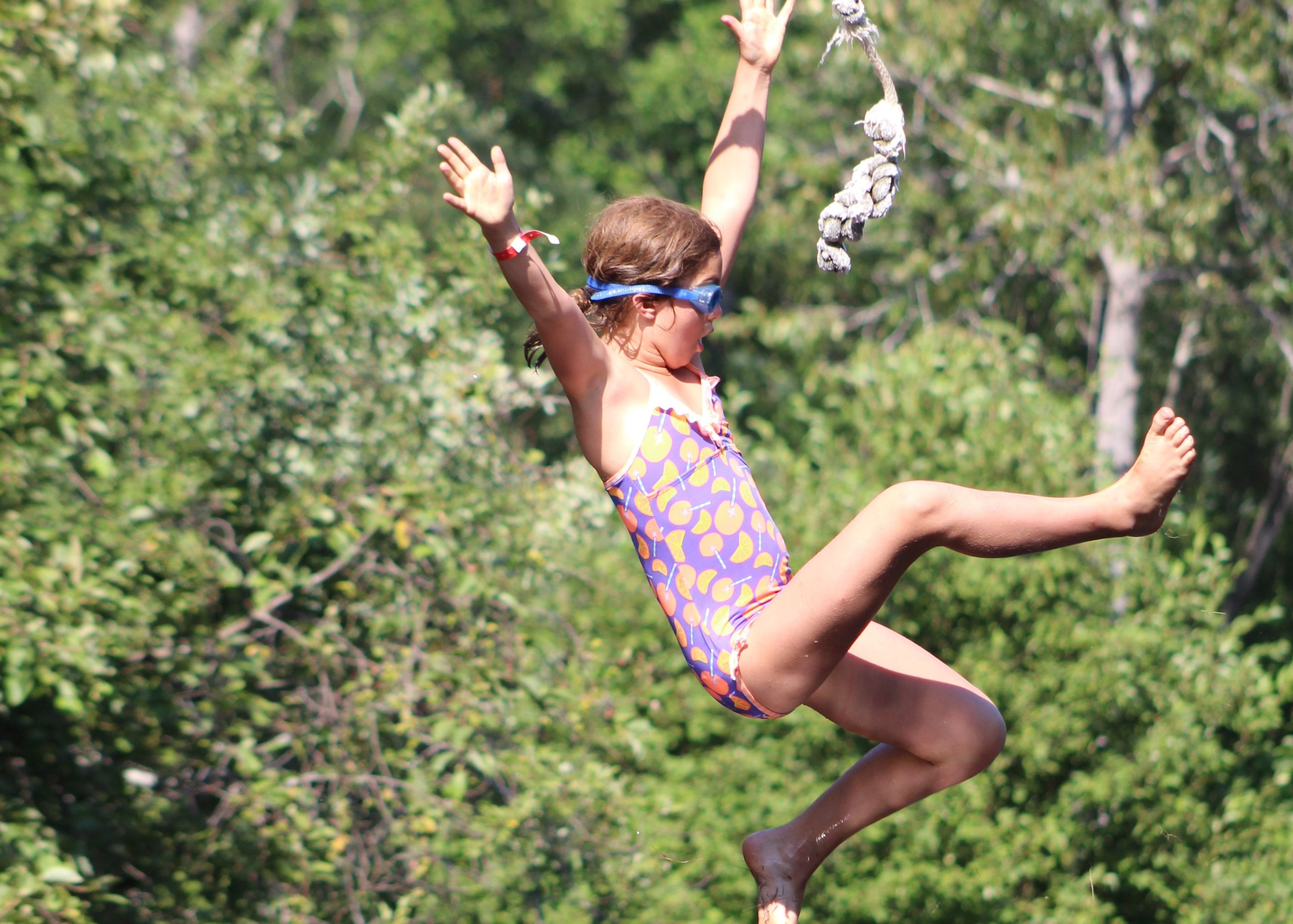 Camper swinging off swing rope into pond at christian adventure summer camp in haliburton, ontario