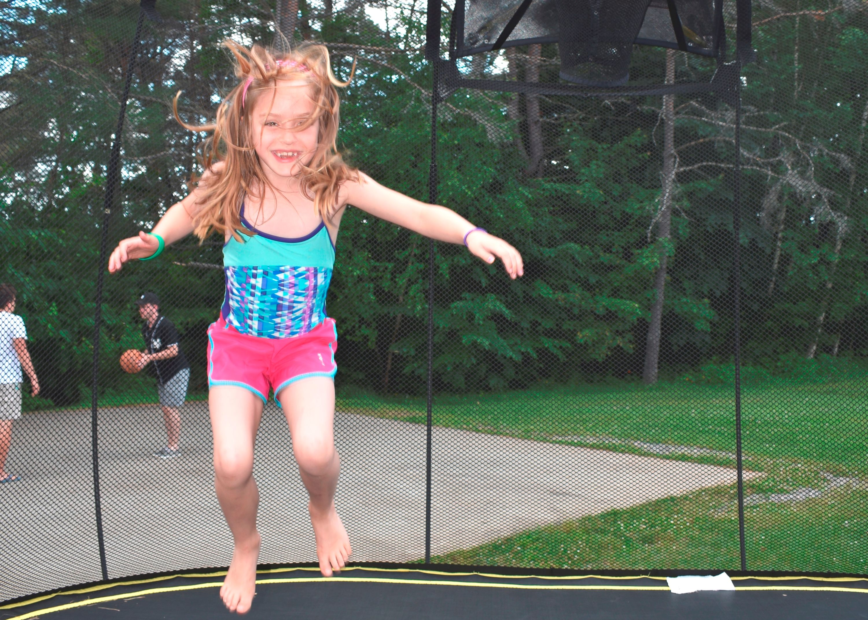 Camper jumping on trampoline at christian adventure summer camp in haliburton, ontario