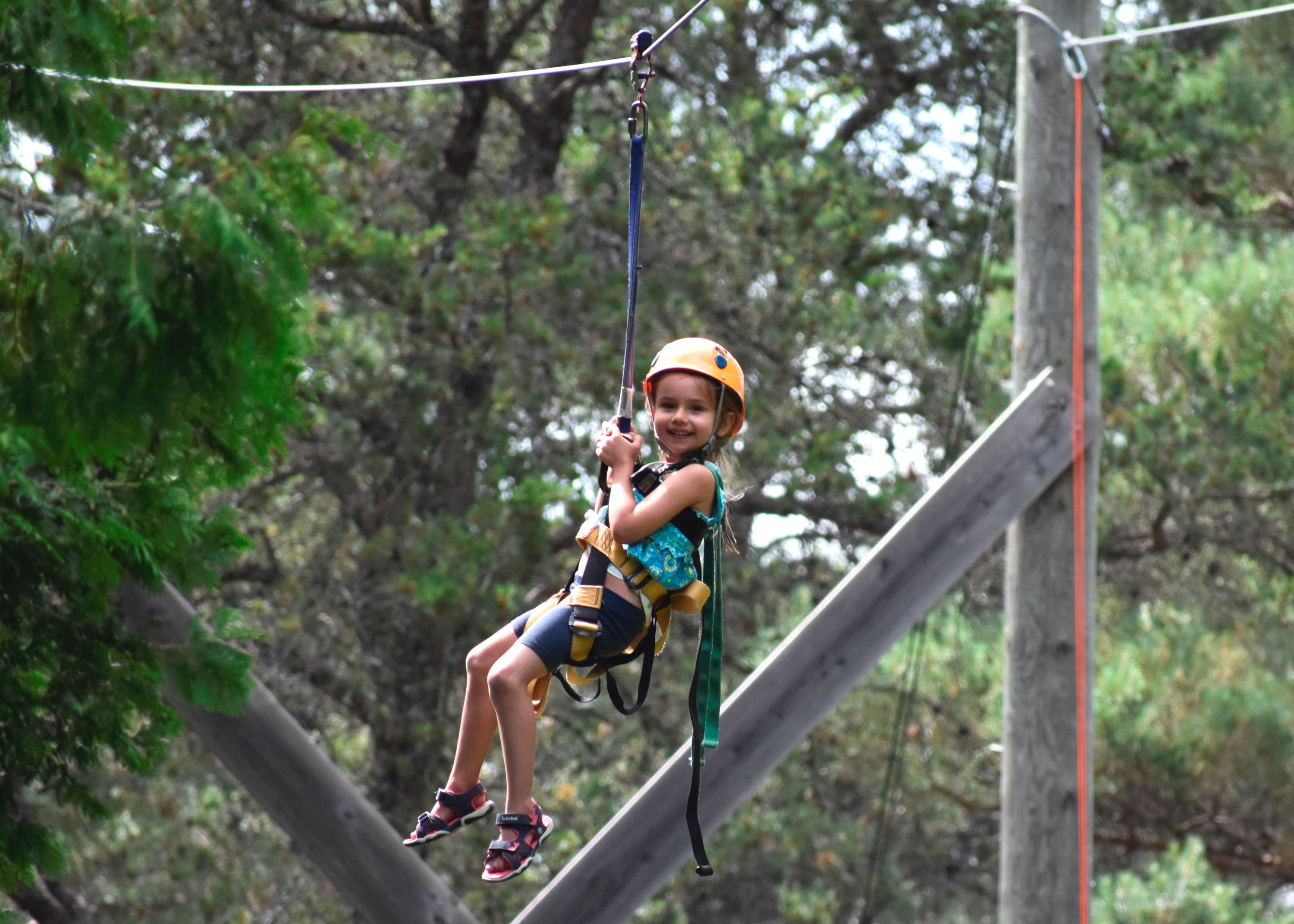 Camper on zipline outside at christian adventure summer camp in Haliburton, Ontario