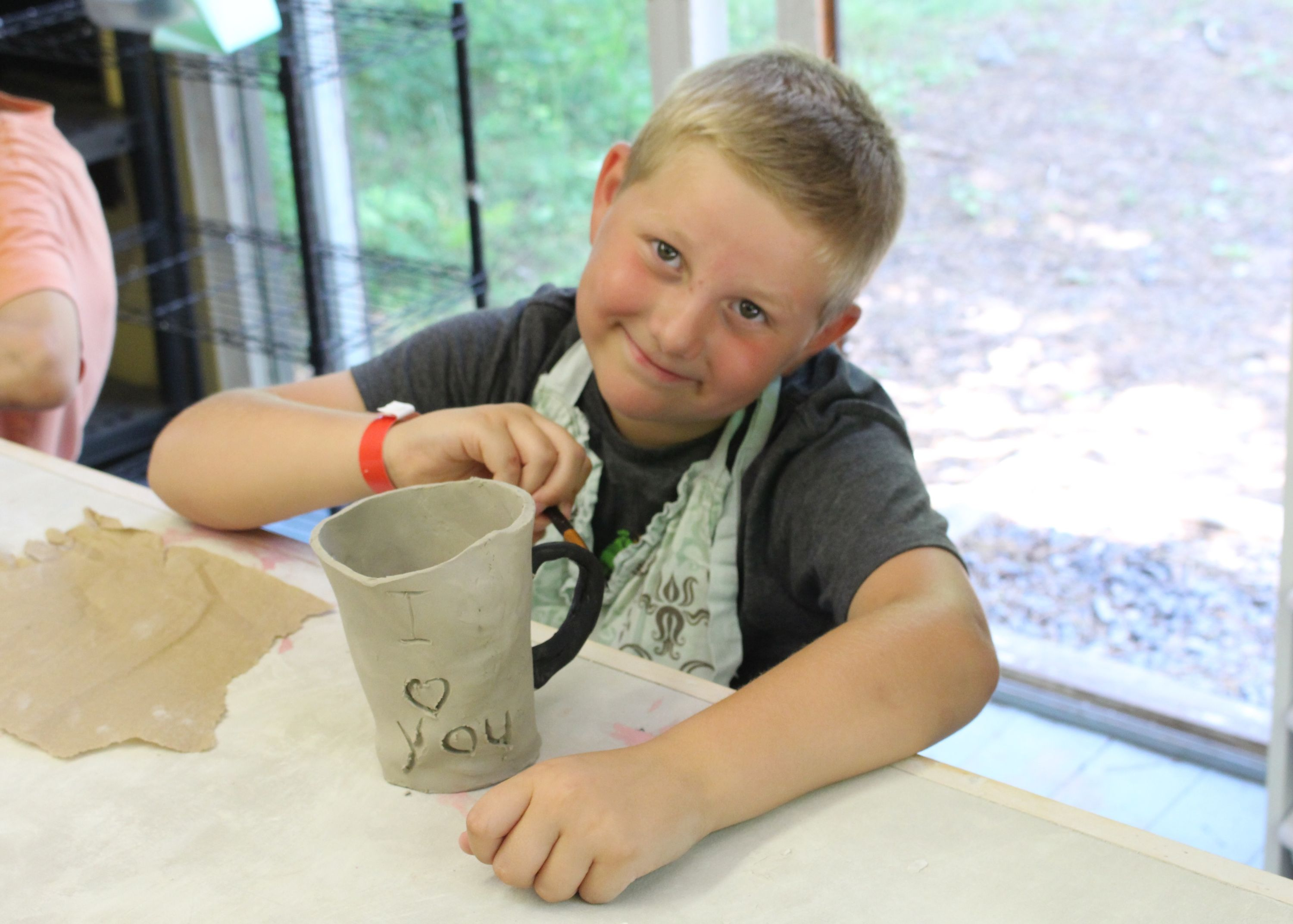 boy showing off his homemade pottery mug, christian Summer Camp