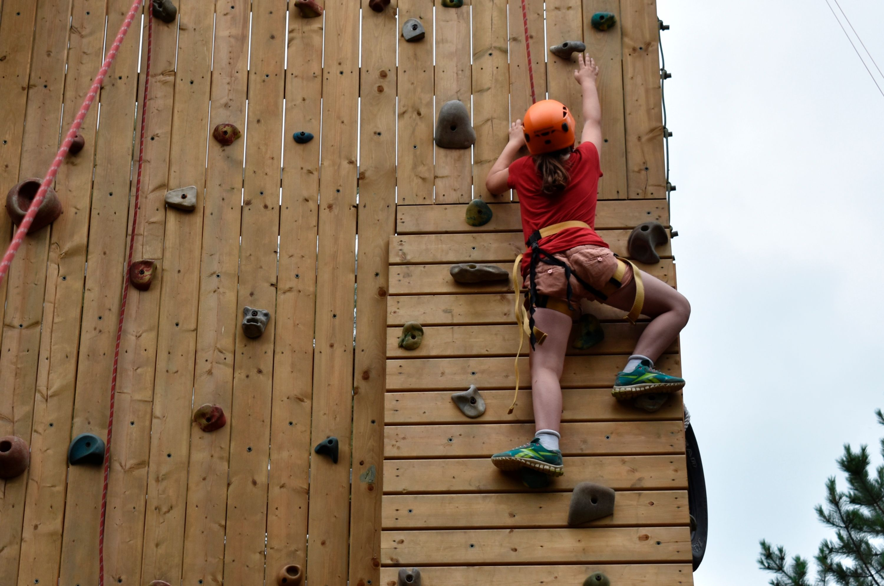 camper climbing on outside rock wall at christian adventure summer camp in haliburton, ontario