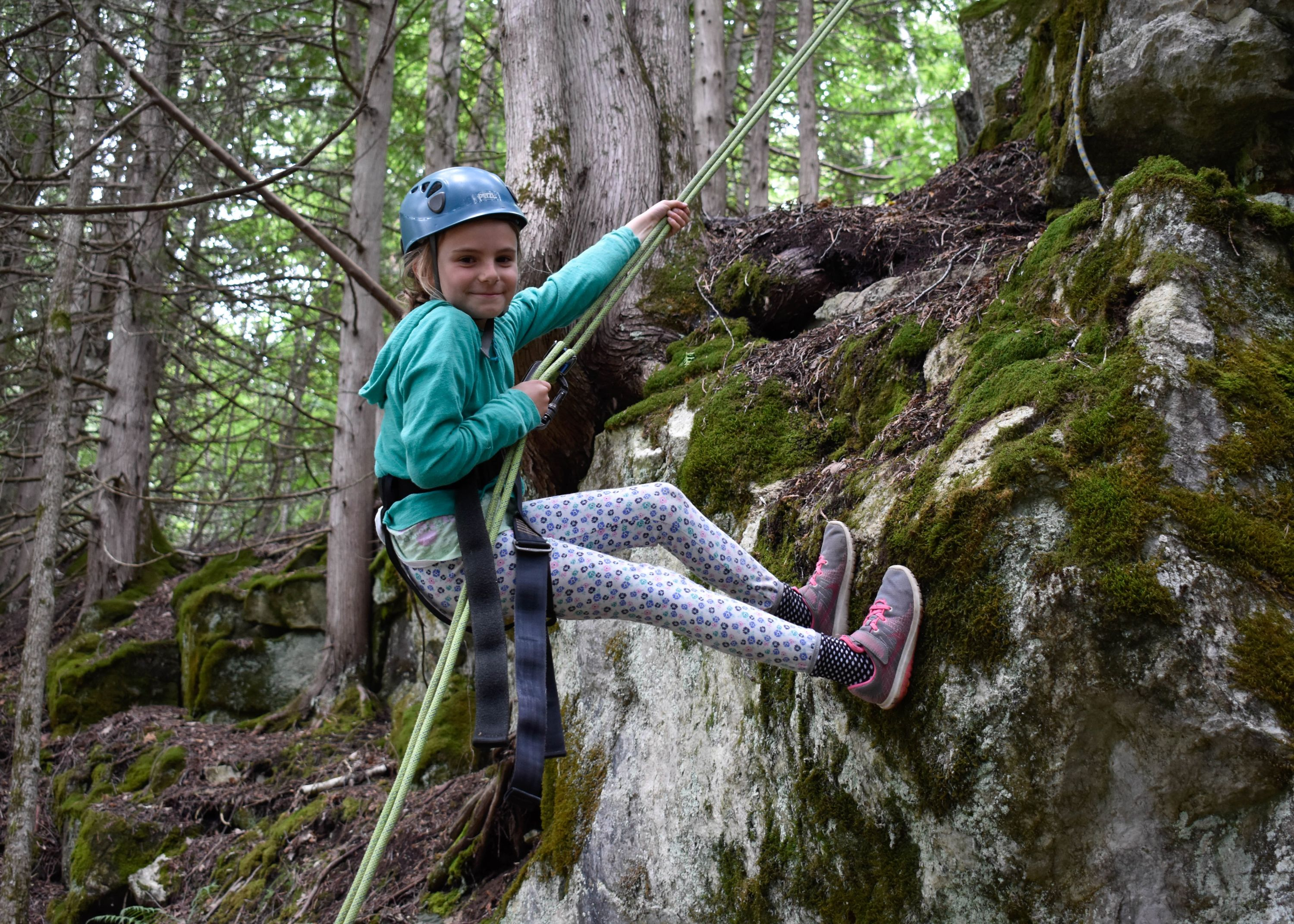 Climber repelling on rock surface for climbing club at christian adventure summer camp in Haliburton, Ontario