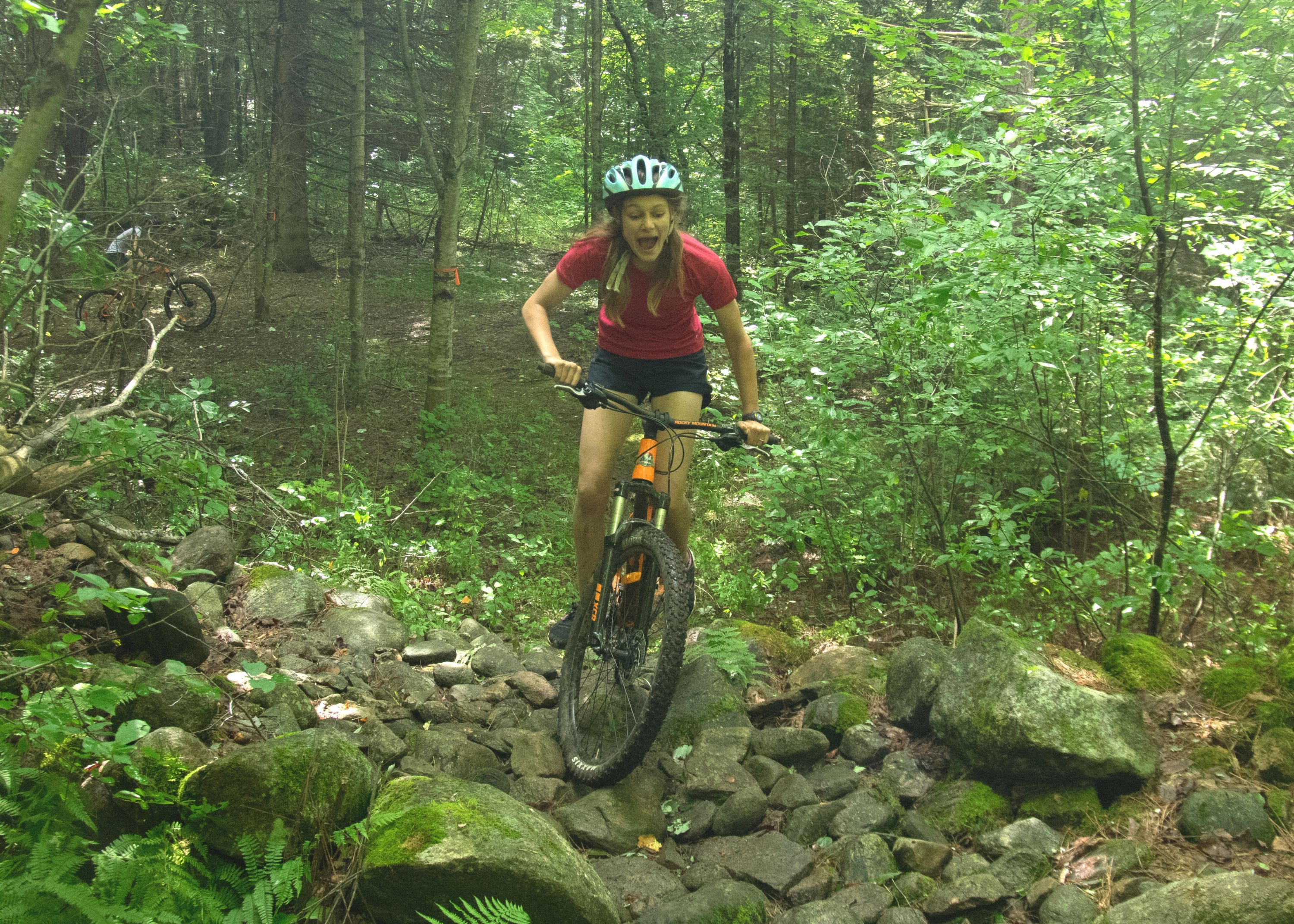 Camper riding mountain bike through forest at christian adventure summer camp in haliburton, ontario