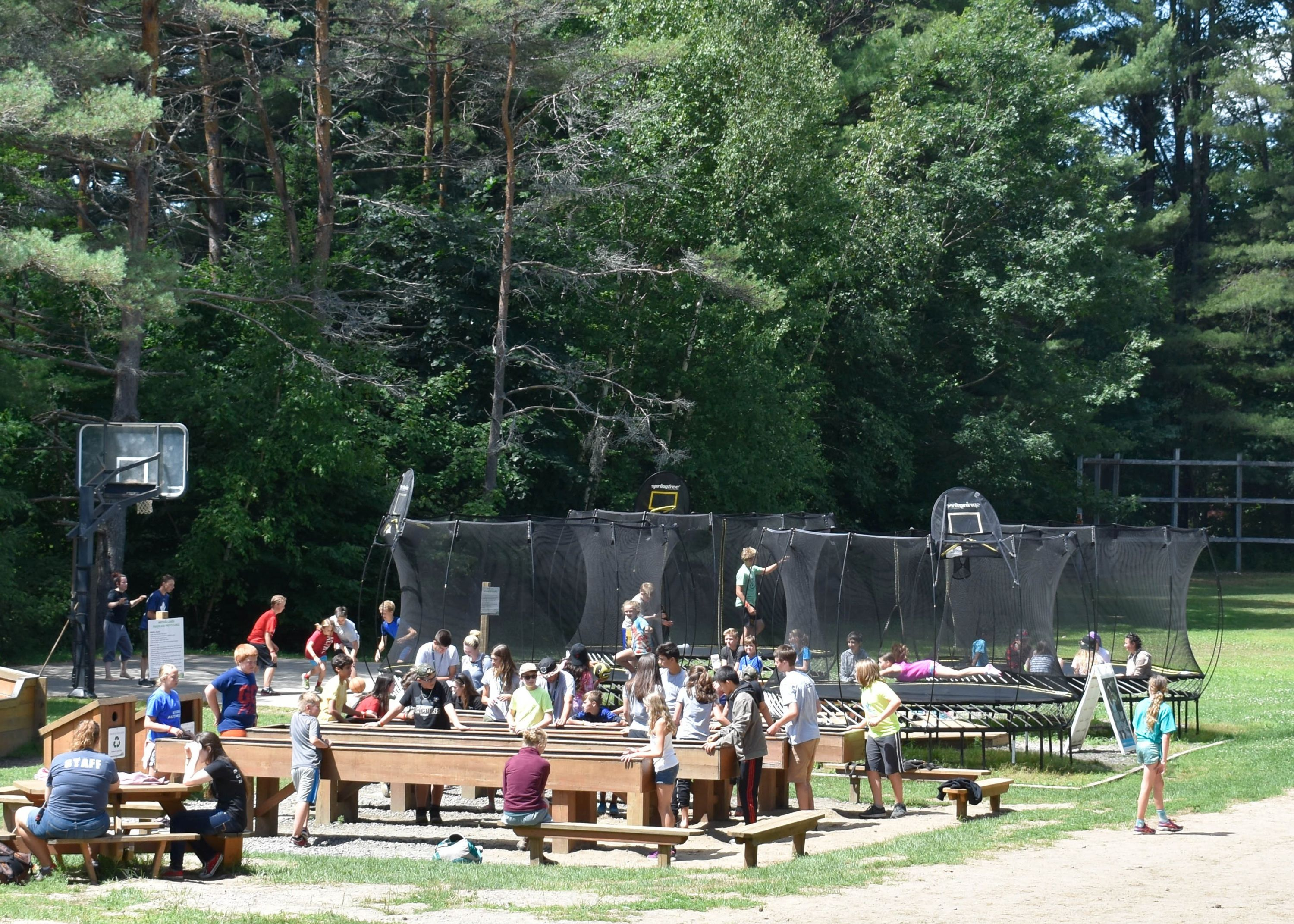 Lots of campers playing in park - trampolines, basketball, octaball, medeba lanes - at christian adventure summer camp in haliburton, Ontario
