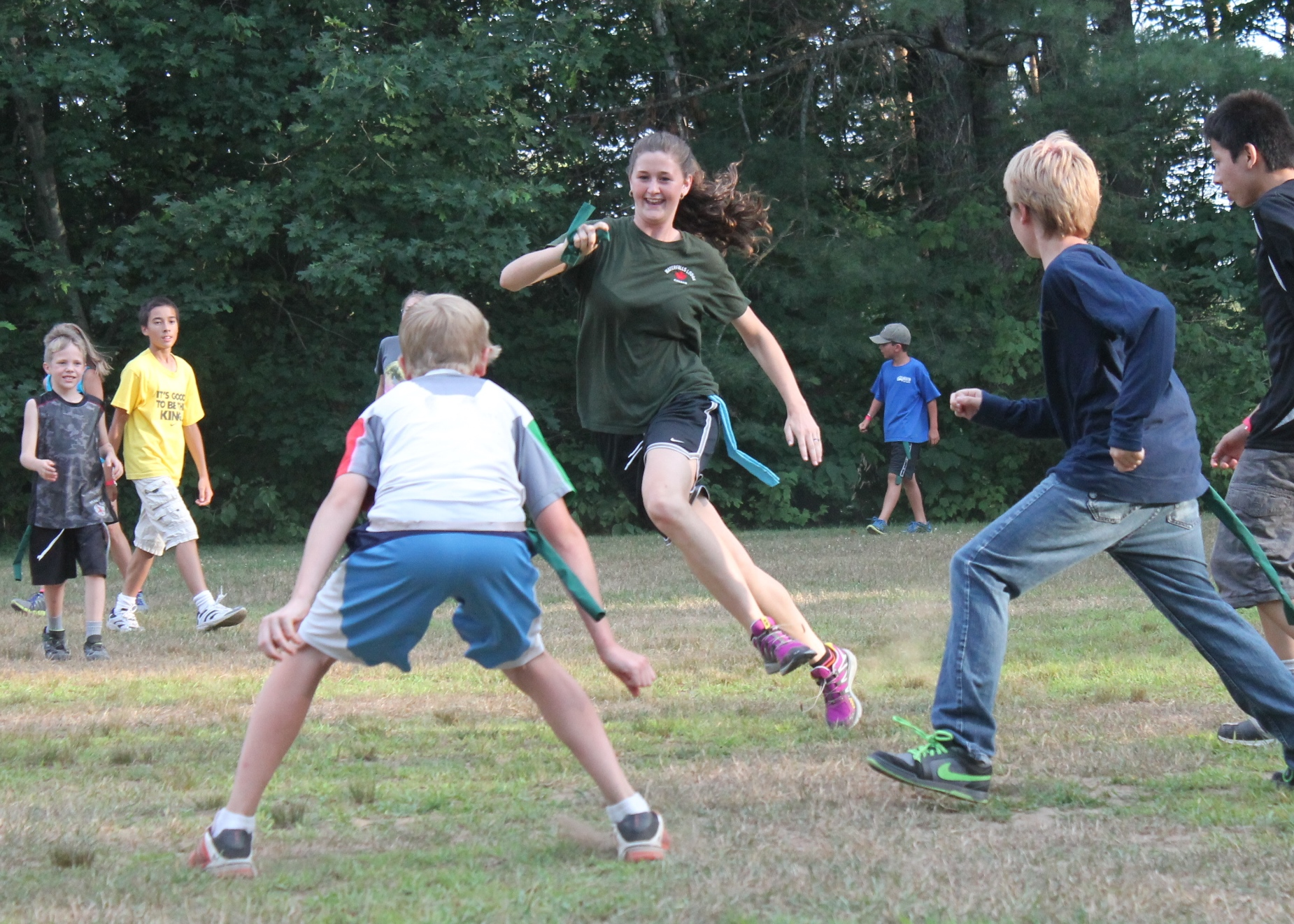 Campers running in field during game at christian adventure summer camp in haliburton, ontario