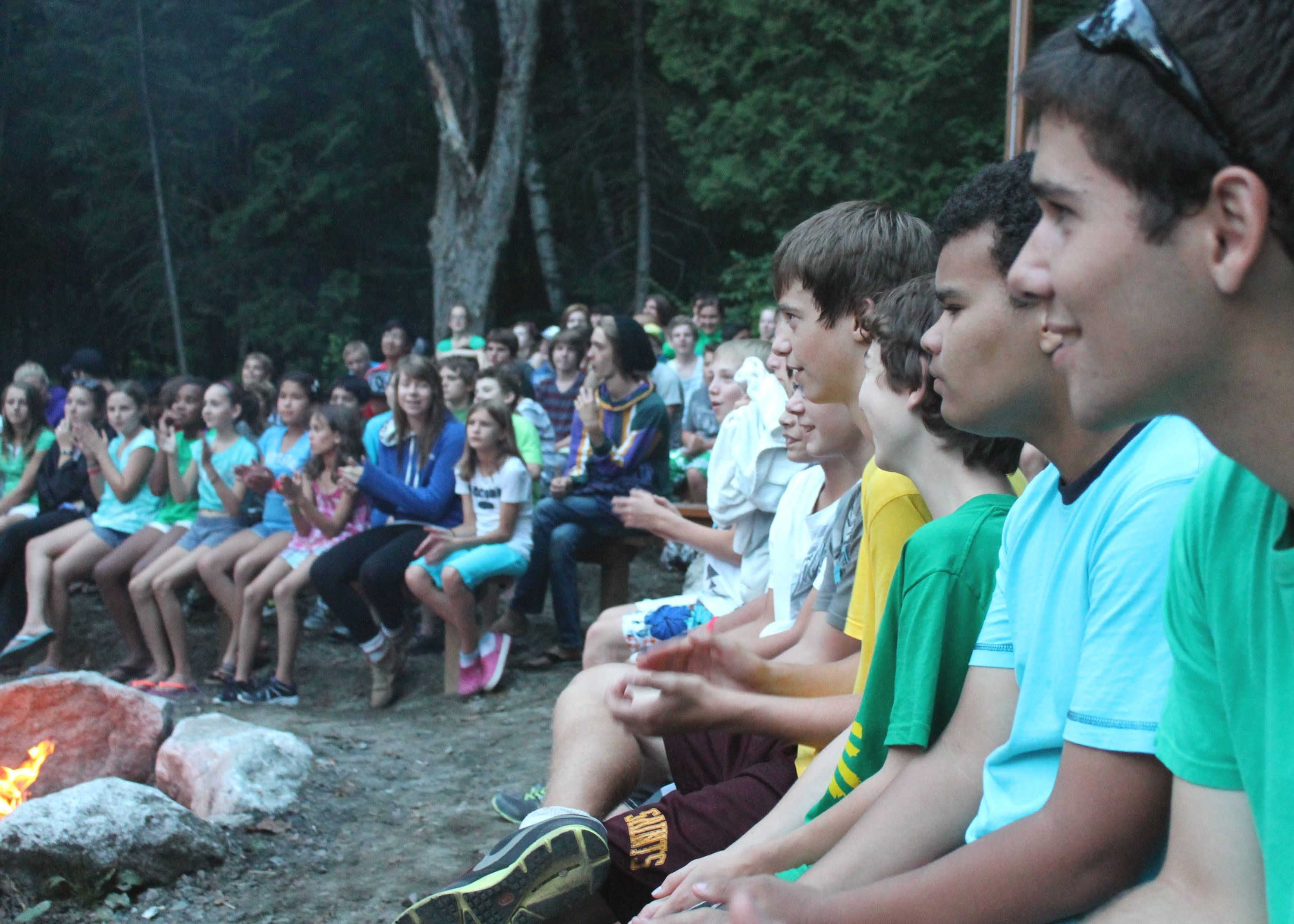 Campers sitting around a campfire at night watching skits and songs at christian adventure summer camp in haliburton, ontario