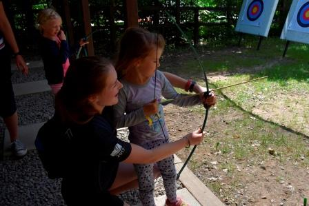 staff teaching a campers how to hold a bow